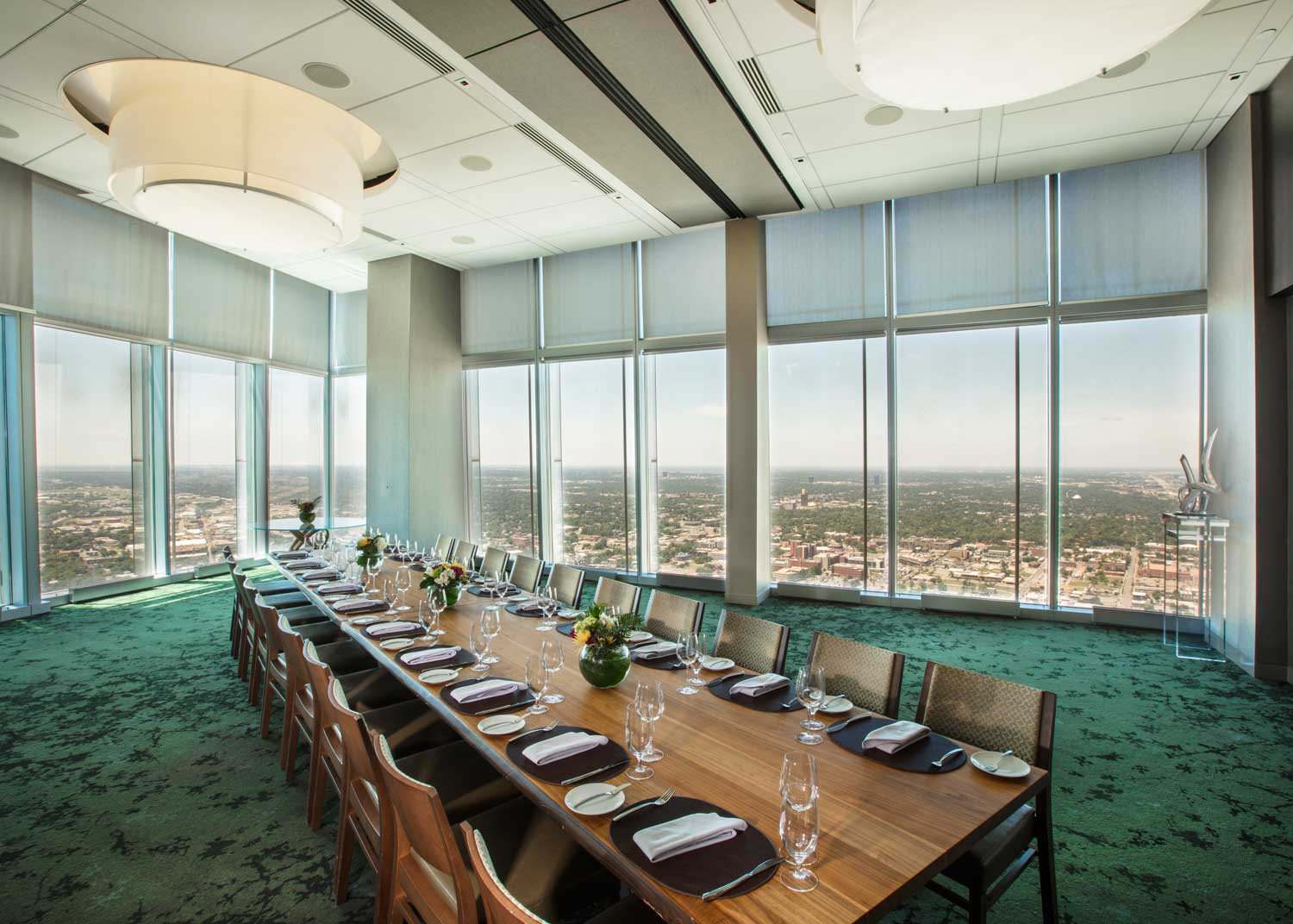 floor to ceiling open meeting space with large boardroom dining table and leather chairs