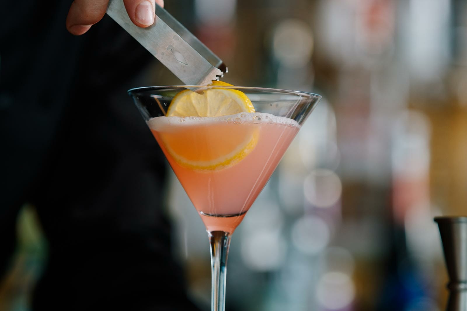 A bartender using tongs to drop a lemon slice garnish in a pink cocktail served in a martini glass