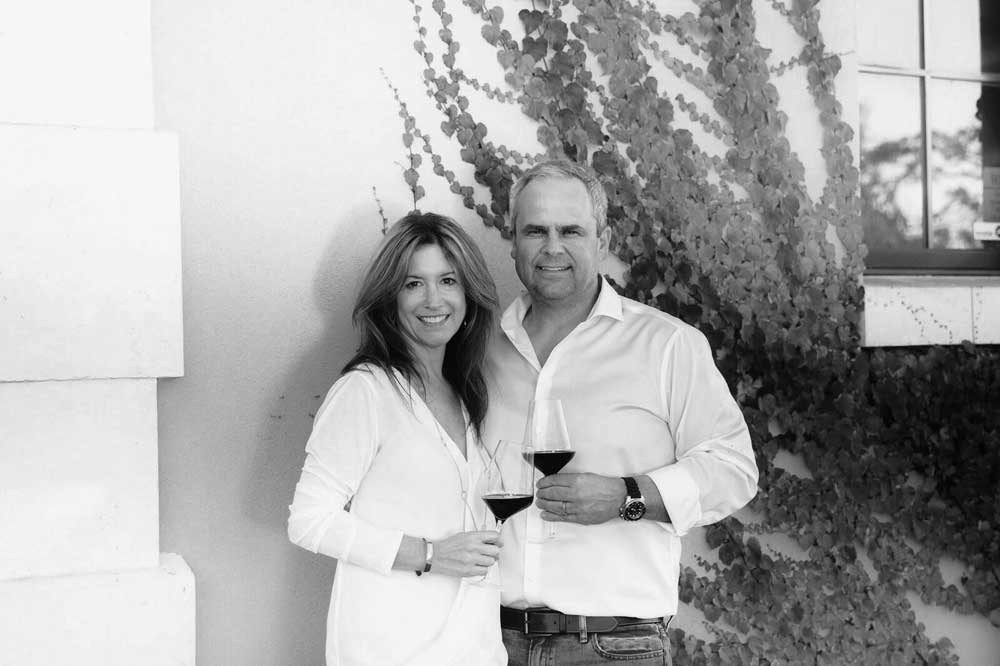 Gus and Paulette Gamba - man and woman smiling at the camera with wine glasses in hand