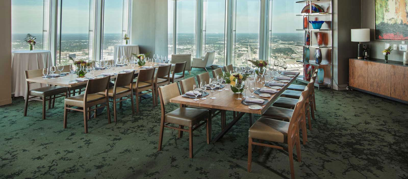 two long dining tables prepared with place settings within an event space with floor to ceiling windows overlooking the city skyline